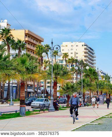 Larnaca, Cyprus - February 18, 2019: Modern Architecture Of Resort City, Car Traffic, Tourists Walki