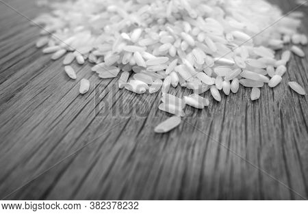 White Rice Isolated On Wooden Board With Blur Effect In Black And White. Food And Ingredients Backgr