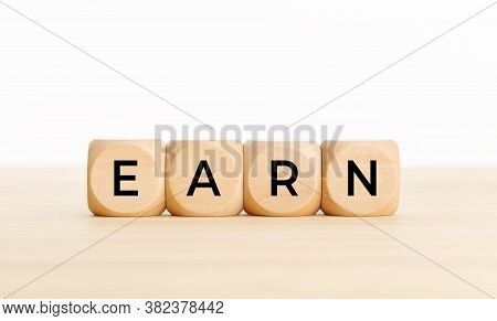 Earn Concept. Wooden Blocks With Text On Table. Copy Space