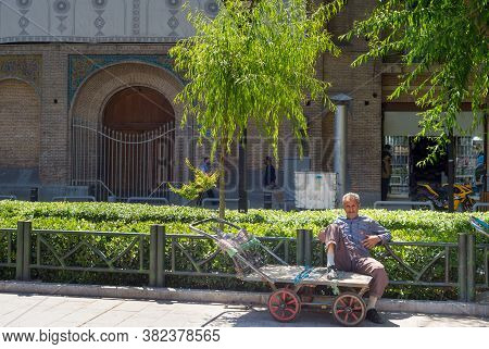 Tehran, Iran - May 22, 2017: Man Sitting On An Empty Cart On The Street Of Tehran. Iran's Unemployme