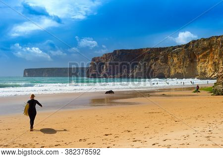 Woman With Surfboard On The Beach. Moody Weather. Algarve, Portugal