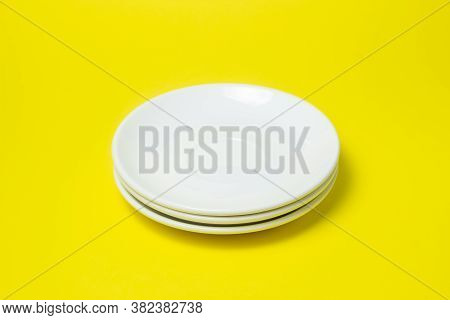 White Plates On A Yellow Background. The Plates Are On Top Of Each Other. Stack Of Plates