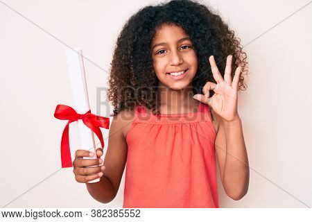 African american child with curly hair holding graduate degree diploma doing ok sign with fingers, smiling friendly gesturing excellent symbol