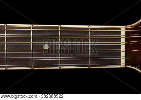 Detail Of A 12 String Guitar Fretboard On Black Background