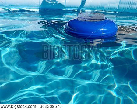 Chlorine Dispenser Floating On A Swimming Pool On A Sunny Day. Chlorine Dispensers Are Used To Disin