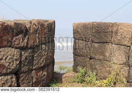 Stone Walls Of An Ancient Fortress. A Narrow Gap Used To Take View Below The Sea Fort.