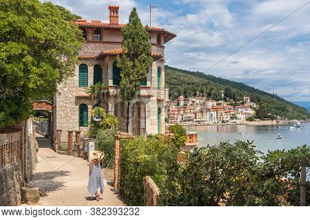 Female Tourist Walking Along Adriatic Sea Coast Relaxing On Vacation In Moscenicka Draga, Istria, Cr
