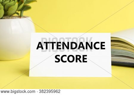 Attendance Score. Text On White Paper On Yellow Background. Flowerpot Book On Background