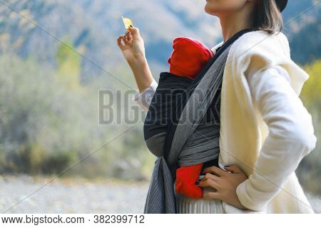 Beautiful Young Mother With Her Infant Baby In Sling Outdoor. Mother Is Carrying Her Child And Trave
