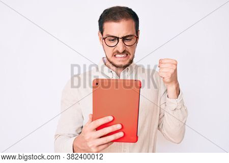 Young handsome man using touchpad device annoyed and frustrated shouting with anger, yelling crazy with anger and hand raised
