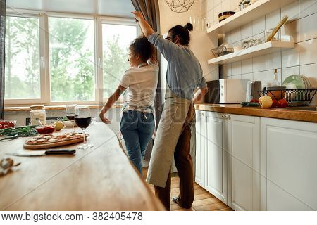 Dance. Young Couple Having Fun, Dancing In The Kitchen While Preparing Dinner At Home. Love, Relatio