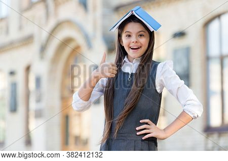 Get Lost In Book. Happy Child Give Thumbs Up Holding Book On Head. Approval Gesture. Hand Sign. Back