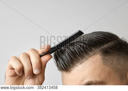 Close Up Young Man Combing His Hair With A Plastic Comb. Styling Hair After Barbershop. Cosmetology