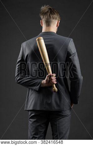 Latent Aggression. Businessman Or Man In Formal Suit Hides Wooden Bat Behind Back, Dark Background.