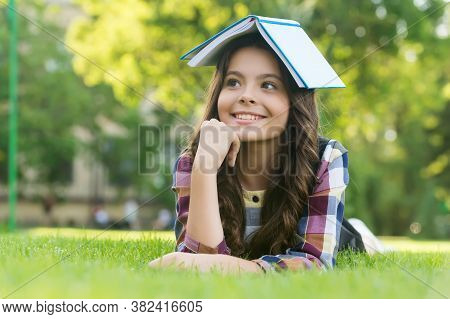 This Is My Reading House. Happy Child Hold Book On Head Lying On Green Grass. Lending Library. Readi