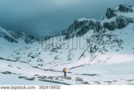 Dressed Bright Orange Jacket Backpacker Man With Trekking Poles And Backpack Trekking By The Mountai