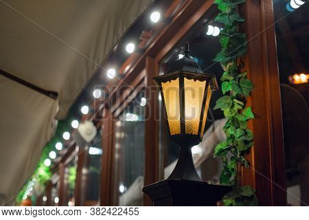 Black Iron Retro Street Lighting Lantern With Glass Shade In Front Of The Building With Wooden Windo