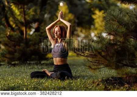 Woman Doing Yoga In The Park. Concentration And Energy Of Nature.
