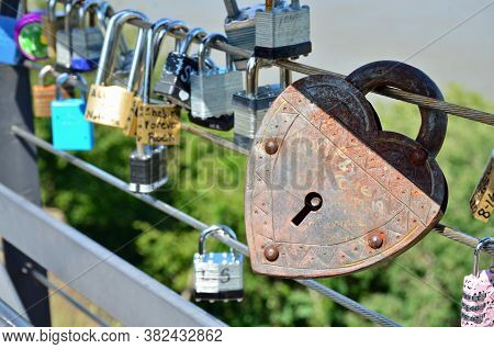 Natchez, Ms - August 24, 2020 A Rusty Heart-shaped Lock Stands Out Among The Locks Placed On The Bri