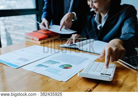 Close Up Businessman And Partner Using Calculator And Laptop For Calculating Finance, Tax, Accountin