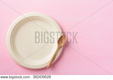Biodegradable Plate, Compostable Plate Or Eco Friendly Disposable Plate And Wooden Spoon On Pink Bac