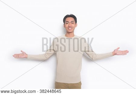 Young handsome man wearing casual beige sweater with khaki pants standing showing both hands open palms,