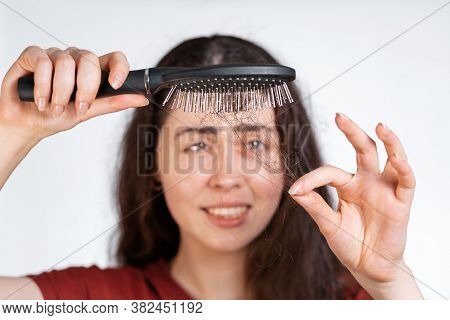 Portrait In A Blur, A Perplexed Brunette Woman Holds A Comb Over Her, Clearing It From A Pile Of Fal