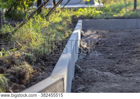Installation Of The Curb Before Laying The Paving Slabs. Reconstruction Of The Sidewalk And Replacem