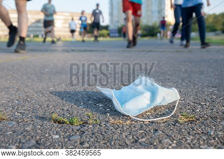 A Dangerous Discarded Anti Virus Breathing Mask Lies On The Road Against The Background Of Passing P
