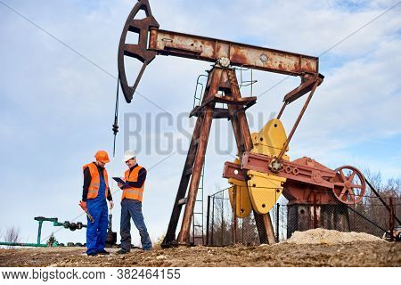 Smiling Extraction Operator Writing On Clipboard While Working With Colleague In Oil Field Near Petr