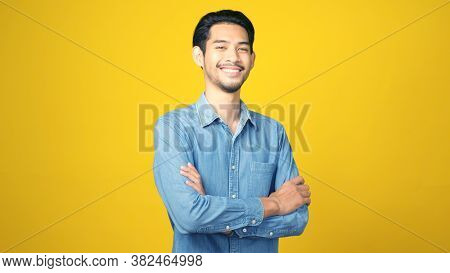 Happy Asian Man Crossed Arms While Standing Over Isolated Yellow Background, Portrait Of Asia Male S