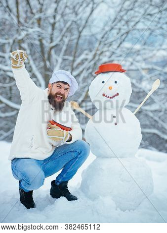Excited Christmas Chef Cook. Snowman And Funny Bearded Man In The Snow Kitchen. Joyful Father Cook H