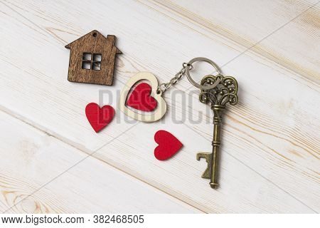 House Key With Home Keyring Decorated With Wooden  Heart.  Old Key With A Heart On White Wood . Swee