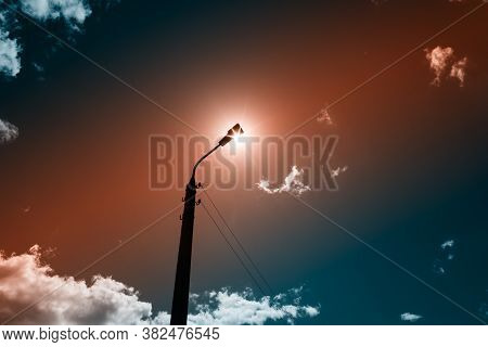 A Lonely Lamppost On The Background Of The Daytime Cloudy Sky. The Sun Is Located Directly Behind Th