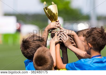 Sport Team Celebrate Success. Happy Boys Rising Golden Cup On Celebration. Kids Winning Sports Schoo