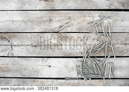 Pile Of Nails On The Old White Wooden Workbench Background With Copy Space.