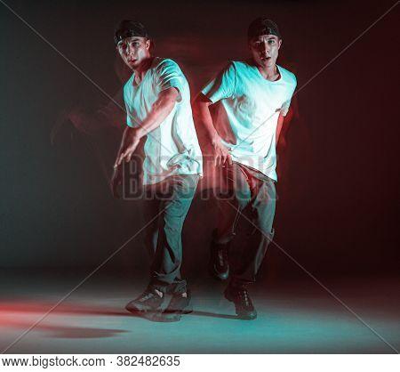 Stylish Young Boy Breakdancer Rapper Dancing Hip-hop In Neon Light. Long Exposure Shot