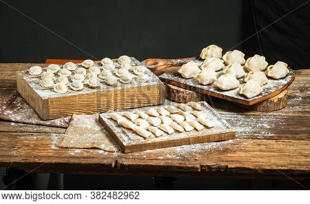 Variety Of Semi-finished Dumplings On The Wooden Boards With Flour