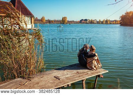 Senior Family Couple Relaxing By Autumn Lake. Happy Man And Woman Enjoying Nature And Hugging Sittin