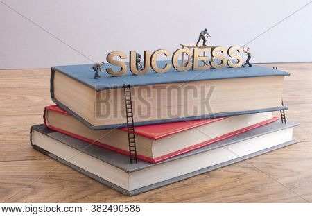 Miniature Construction Builders Working Around The Golden Heading Succcess On Top Of A Stack Of Book