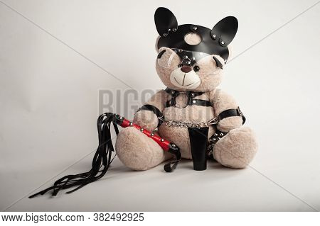 Toy Bear Dressed In Leather Belts Harness Accessory For Bdsm Games On A Light Background