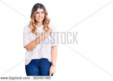 Young caucasian woman wearing casual clothes pointing aside worried and nervous with forefinger, concerned and surprised expression
