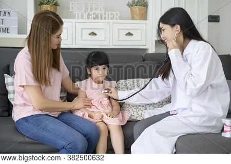 A Female Doctor Holding Stethoscope Is Examining A Happy Girl In The Hospital With Her Mother, Medic