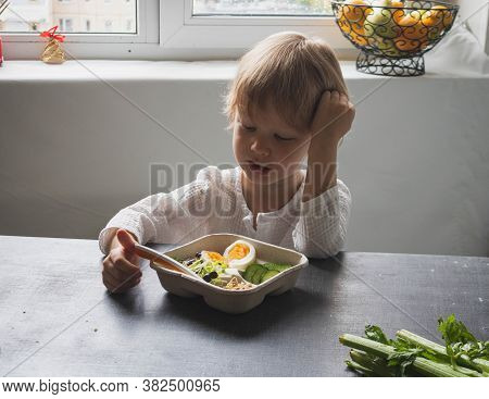 Sad Child Boy Sadly Picks A Plate Of Healthy Food With A Spoon. Difficulty Feeding Children. The Chi