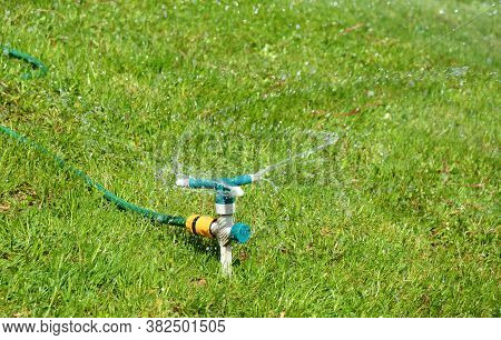 A Close-up On A Three Arm Garden Sprinkler, Rotating Garden Sprinkler System With A Hose Watering A
