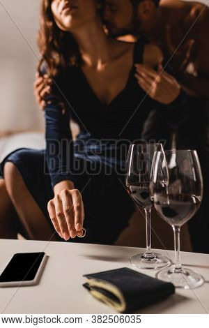 Cropped View Of Woman Putting Wedding Ring Near Smartphone And Glasses Of Wine On Coffee Table While
