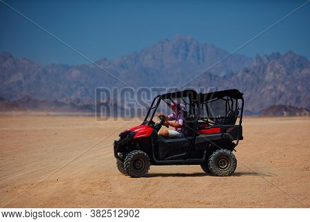 Excited Man Driving A Buggy In A Desert. Extreme Tour