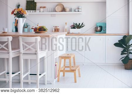 A Cozy Modern Kitchen Room Interior With Island Counter, Wooden Furniture And Wall Shelves