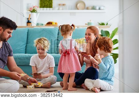 Happy Family Playing Card Game Together On The Floor At Home