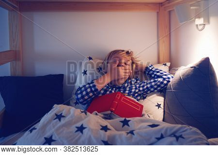 Young Boy Yawning While Laying In The Bed And Reading A Book Before Going To Sleep